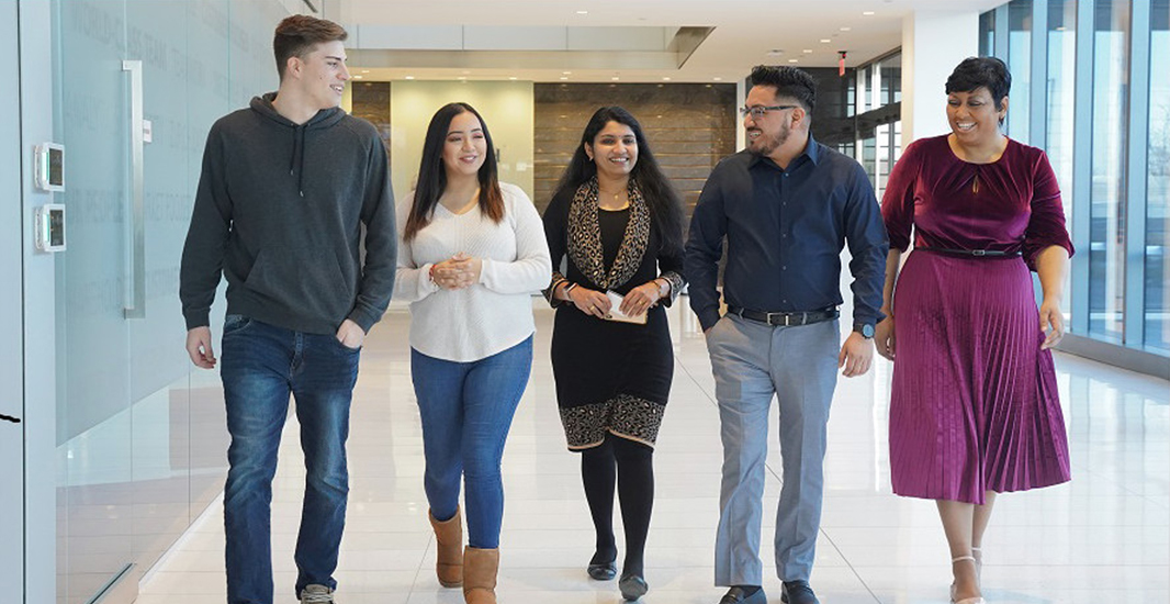 On the job: Zurich apprentices (from left): Jordan West, Liz Rodriguez, Sreelekha Sathiyamma, Jose Gonzalez and Trinette Patterson head to the coffee bar at Zurich North America's headquarters in Schaumburg, Illinois, in February 2020. Sathiyamma graduated from the program in November 2020 and is now a Zurich cybersecurity analyst. Photo courtesy of Zurich North America.