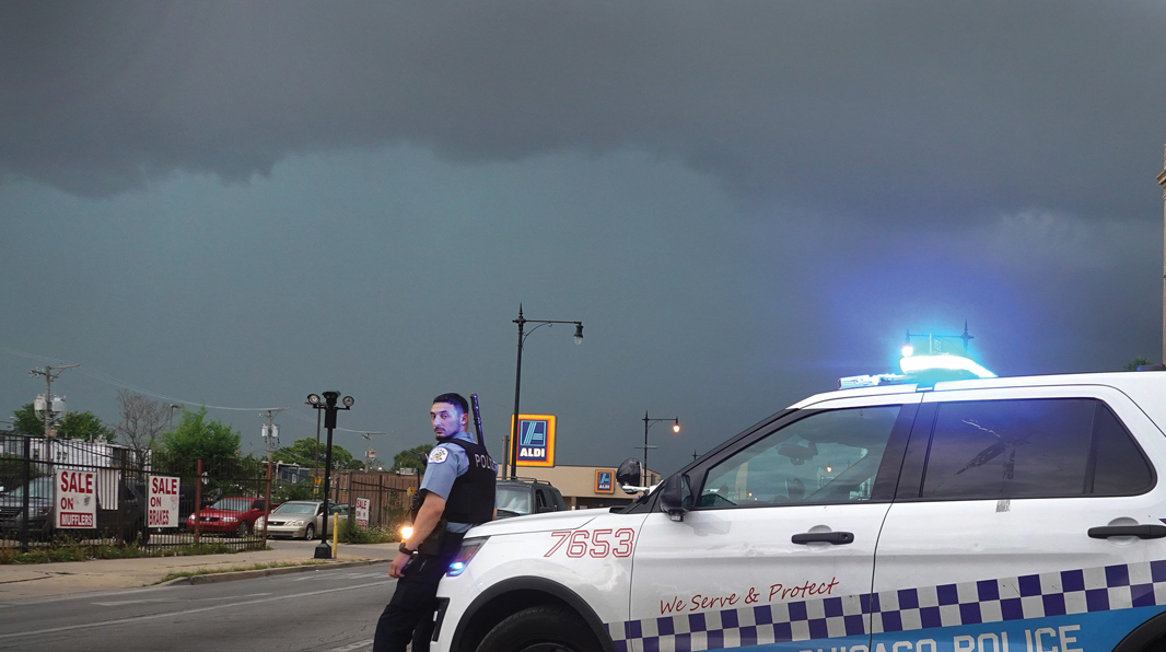CHICAGO: A police officer stands guard following unrest on the city's West Side moments before a derecho hits the area on Aug. 10, 2020. The storm, with wind gusts close to 100 mph, downed trees and power lines as it moved through the city and suburbs.